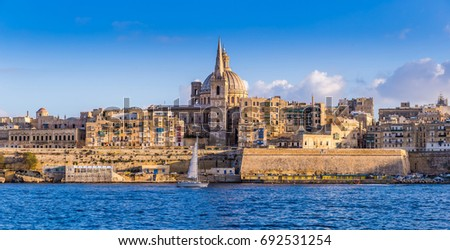 Valletta, Malta - Panoramic view of Saint Paul's Cathedral and the ancient walls of Valletta with sail boat in the morning