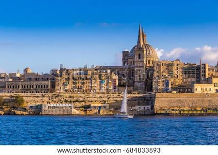 Valletta, Malta - Saint Paul's Cathedral and the ancient walls of Valletta with sail boat in the morning
