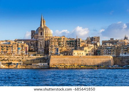 Valletta, Malta - The beautiful Saint Paul's Cathedral and the ancient walls of Valletta in the morning with clear blue sky