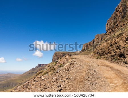 Valley and winding road over mountains from South Africa to Lesotho over Sani Pass - stock photo