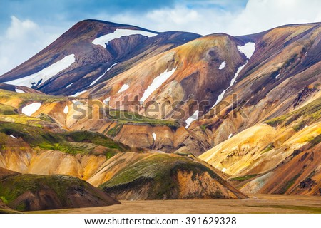 Valley National Park Landmannalaugar. On the gentle slopes of the mountains are snow fields and glaciers. Magnificent Iceland in the July - stock photo