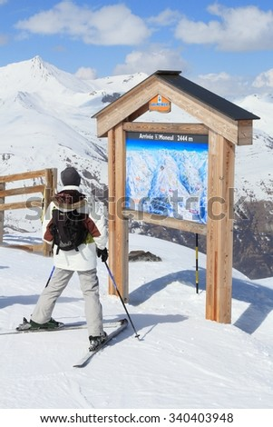 VALLOIRE, FRANCE - MARCH 24, 2015: Skier analyzes ski map in Galibier-Thabor station in France. The station is located in Valmeinier and Valloire and has 150km of ski runs. - stock photo