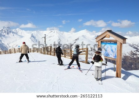 VALLOIRE, FRANCE - MARCH 24, 2015: Skiers analyze ski map in Galibier-Thabor station in France. The station is located in Valmeinier and Valloire and has 150km of ski runs.