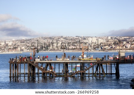 VALPARAISO-APRIL 3,2015: Some people fishing off the side of the pier in Valparaiso, face the downtown cityscape across Valparaiso Bay on april 3, 2015 in Chile