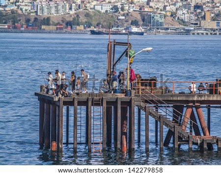VALPARAISO, FEBRUARY 11: People fishing on a pier in the bay with the city on background on February 11, 2011 in Valparaiso, Chile. - stock photo