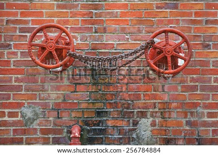 Valve wheels with chain link covered in ice from winter ice storm - stock photo