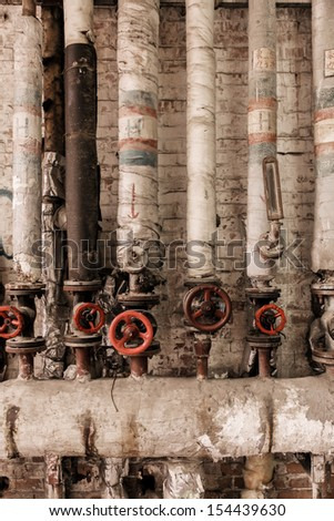 Valves of old steam at factory - stock photo