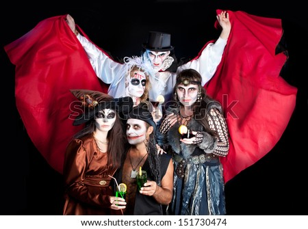 vampire and a joker with witches posing over dark background. Halloween - stock photo