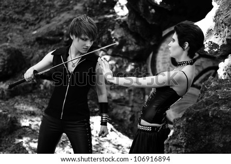 vampire and young warrior woman with sword - stock photo
