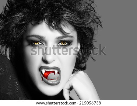 Vampire. Beautiful young woman with fancy makeup, bloody fangs and wolf lenses. Halloween concept. Black and white portrait with copy space - stock photo