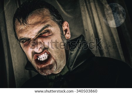 Vampire Bloody Face Moon. Horror male vampire portrait, edited with vintage film effects and the moon. - stock photo