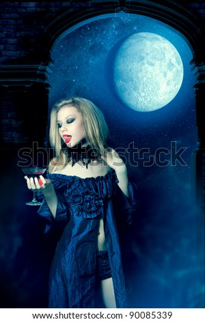 Vampire girl in a dress with glass of wine