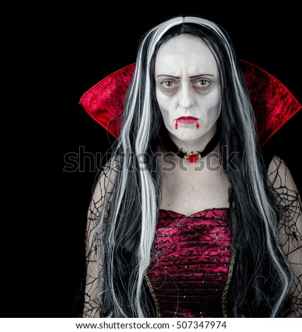 Vampire Halloween Woman portrait. Vampire Girl with dripping blood from her red lips. Vampire makeup and costume for Halloween party. Black background with copy space.