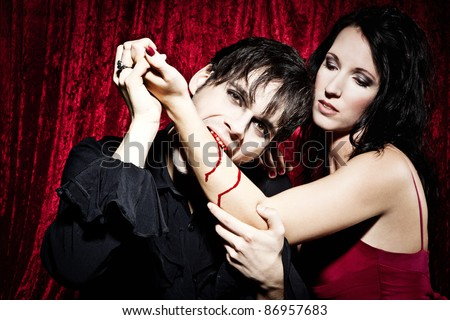 Vampire is sucking out his prey - stock photo
