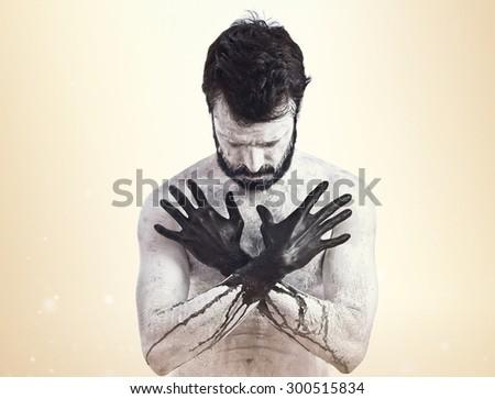 Vampire with black hands over ocher background - stock photo