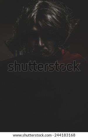 Vampire with red coat and long hair, halloween - stock photo