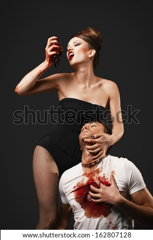 Vampire woman eating man heart - stock photo