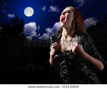 Vampire woman on night background with moon - stock photo