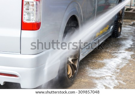 Van Car wash by high pressure cleaners, focus on the car