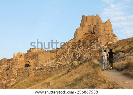 VAN, TURKEY-JULY 29, 2011:  Visitors hike up to the Fortress of Van, overlooking the ruined capital and Lake Van.  It was built by the ancient kingdom of Urartu between the 9th to 7th century.   - stock photo