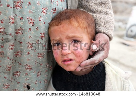 VAN, TURKEY - OCTOBER 25: Earthquake victim boy at the earthquake of Van-Ercis on October 25, 2011 in Van, Turkey. It is 604 killed and 4152 injured in Van-Ercis Earthquake. - stock photo