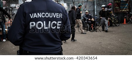 VANCOUVER, BC, CANADA - MAY 11, 2016: Vancouver police officer on patrol in an area of heavy drug use and poverty which is Vancouver's Downtown Eastside.
