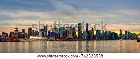 Vancouver BC, Canada. Night, glowing with multicolored lights, the megacity of the ocean with huge new-modern buildings and blue sky