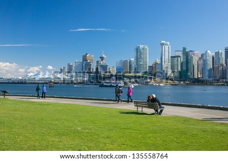 VANCOUVER, CANADA - APRIL 14: Unidentified people walk on seawall in Stanley Park on April 14, 2013. Seawall is 8.8-kilometer paved route that loops around the park. - stock photo