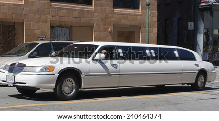 VANCOUVER, CANADA - AUGUST 6, 2005: Lincoln Town Car Stretch Limousine driving through Downtown Vancouver. They are often hired during special events like weddings or funerals. - stock photo