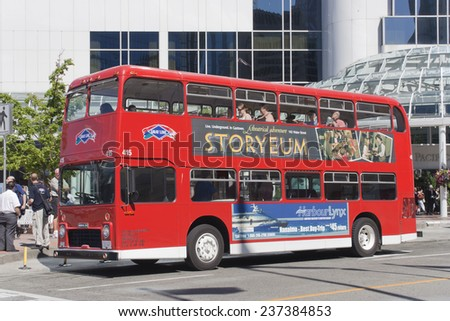 VANCOUVER, CANADA - AUGUST 6, 2005: Red double-decker bus standing on bus stop in Vancouver, Canada. Tourists enjoy a Vancouver Sightseeing Tour. In the background the Pan Pacific Hotel.