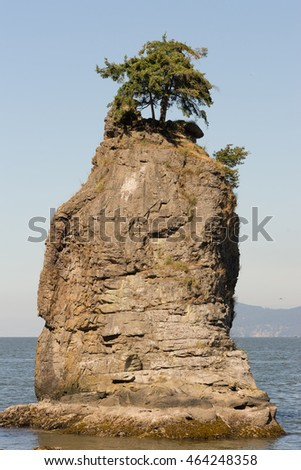 Vancouver, Canada - July 24, 2016: Portrait of the iconic Siwash Rock which stands in the ocean a few meters off Stanley park. Clear skies