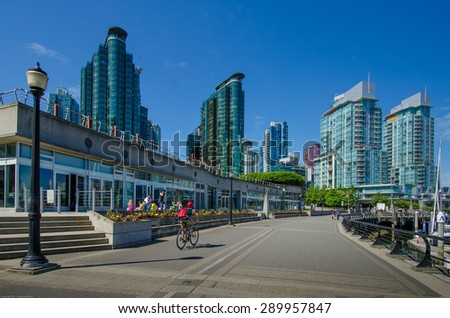 VANCOUVER, CANADA - JUNE 17, 2015: Young man bikes along the boardwalk of the waterfront with the city skyline in the background.