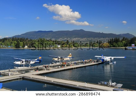 VANCOUVER, CANADA - May 07, 2015: Row of seaplanes and unidentified maintenance personnel at the Vancouver Harbour Flight Centre. Centre is conveniently located for travelers with access to hotels. - stock photo