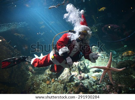 VANCOUVER, CANADA - NOVEMBER 27, 2014: Scuba diving Santa Claus swims amongst the fish in the tank at the Vancouver Aquarium to mark the beginning of Christmas season, Nov.27, 2014, Vancouver, Canada. - stock photo