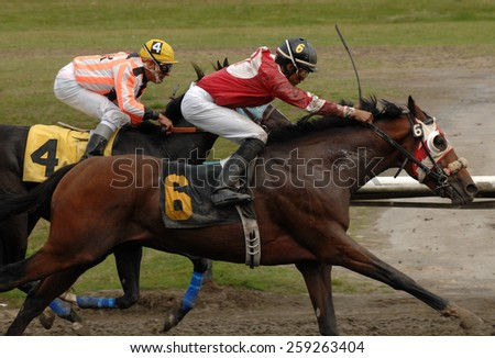 VANCOUVER, CANADA - SEPTEMBER 9, 2014: Horses ridden by jockeys compete at Hastings Park in Vancouver, Canada, on September 9, 2014. - stock photo