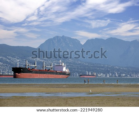 Vancouver, English Bay - wide Spanish Banks beaches with with two oceangoing freighter - stock photo