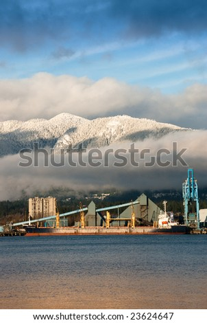 Vancouver Harbor, a cargo ship docked in front of shoreline industry with water reflecting yellow in the foreground.  Behind the industry is rows of clouds with snow covered mountains and a blue sky. - stock photo