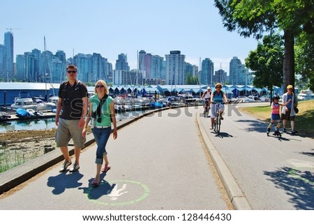 VANCOUVER - JULY 05: People at  Stanley Park  Seawall on July 05, 2008 in Vancouver Canada. Famous seawall where park visitors walk, bike, roll, and fish on the 22 kilometers seawall route. - stock photo