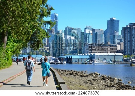 VANCOUVER - JULY 27: People at Stanley Park Seawall on July 27, 2014in Vancouver Canada. Famous seawall where park visitors walk, bike, roll, and fish on the 22 kilometers seawall route. - stock photo