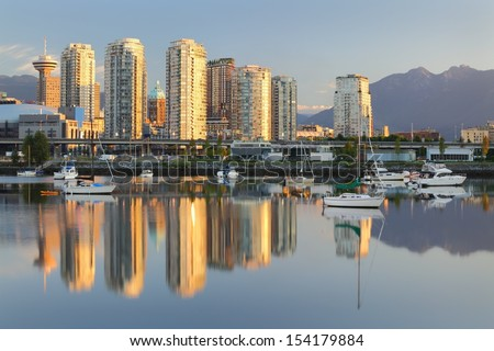 Vancouver Sunrise Reflection, False Creek. An early morning view of downtown Vancouver's skyline and the Coast Mountains reflected in the still waters of False Creek. British Columbia, Canada.  - stock photo