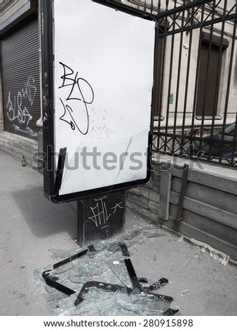 vandalism in the street - an advertisement stand with broken glass - stock photo