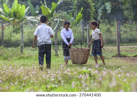 VANG VIENG, LAOS - 7 December 2012: Childrens picking garbage in the school.