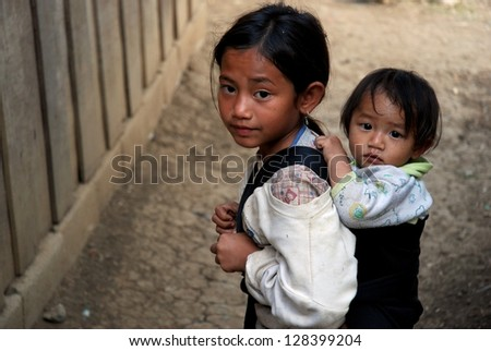 VANG VIENG, LAOS - JANUARY 22 : Unidentified kids in Vang Vieng, Laos on January 22, 2009. Vang Vieng is a tourism-oriented town in Laos, about four hours bus ride north of the capital. - stock photo