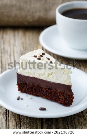 Vanilla and chocolate cake on wooden background.