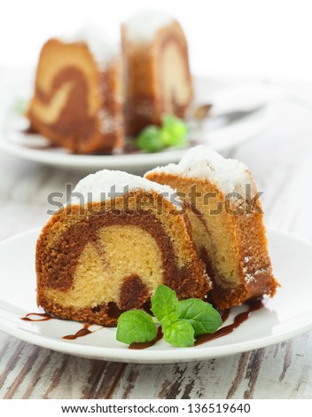 Vanilla and chocolate cake sliced with mint laves  on wooden table - stock photo