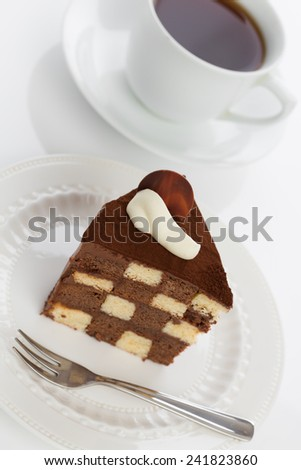 Vanilla and chocolate checkerboard cake makes a perfect tea time treat! The cake is garnished with whipped cream and cocoa powder, frosted with chocolate ganache. Shot with creative angle. - stock photo