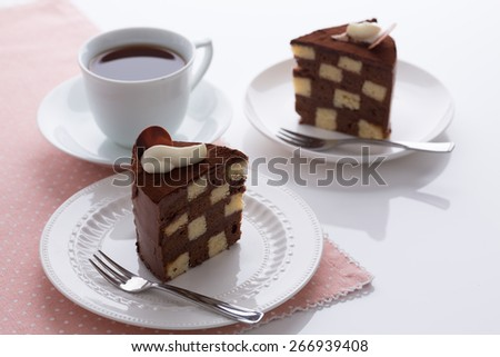 Vanilla and chocolate checkerboard cake makes a perfect tea time treat! The cake is garnished with whipped cream and cocoa powder, frosted with chocolate ganache. Shot with low key lighting. - stock photo