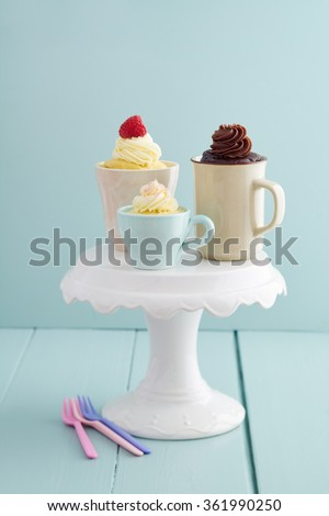 Vanilla and chocolate mug cakes with frosting  and raspberries on a cake stand - stock photo
