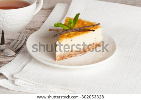 Vanilla cheesecake on a white plate and cup of tea, close up, horizontal - stock photo