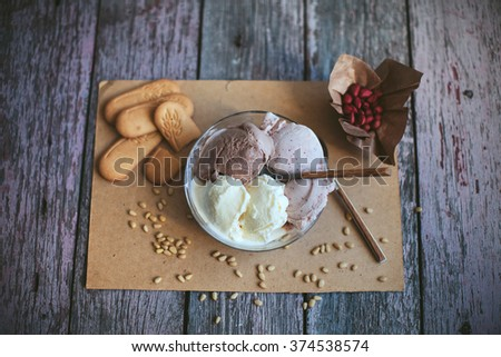vanilla, chocolate, berry ice cream in a bowl with a spoon on a wooden table with nuts and biscuits - stock photo